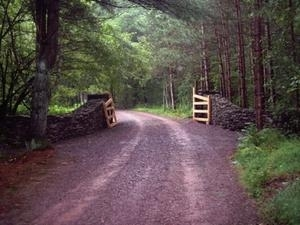 A private road with a rustic stone gate defines the entrance