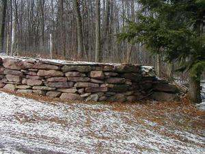 A dry-stacked fieldstone wall in the winter. This curved wall adds some