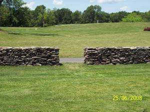 A free standing dry-stacked stone wall with an open gateway.