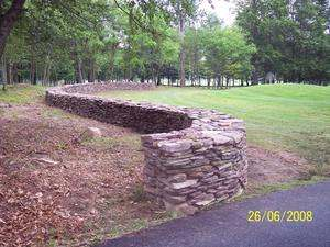A free standing dry-stacked wall with nice flowing curves meanders across this property.