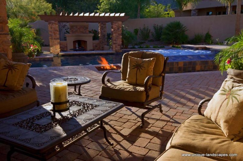 Beautiful patio brickwork, tile, and natural stone pillars surround this backyard pool.