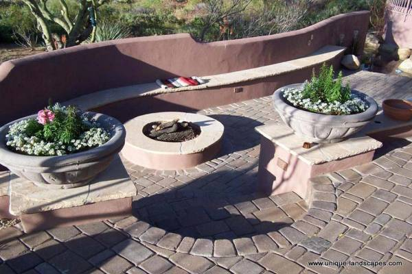 Seating built into the wall makes for a cozy little sunken firepit area off the main patio.