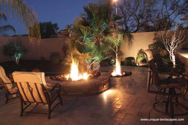 A light show of flames and shadows dance around this patio and onto the walls behind the palm.