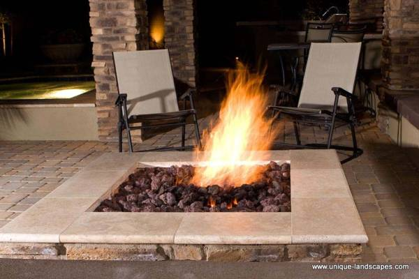 This firepit is set just off an outdoor kitchen and a hot tub.