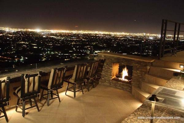 Watching over the city lights on a formal deck, with the warmth of an outdoor fireplace at your side.
