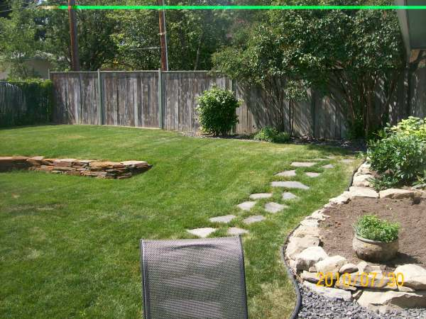 A stepping stone pathway leads from the patio to a back gate.