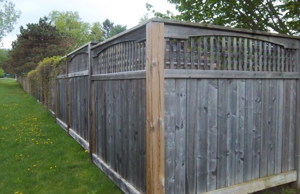 This standard board fence has some added appeal with a molding style wooden cap on top of lattice.