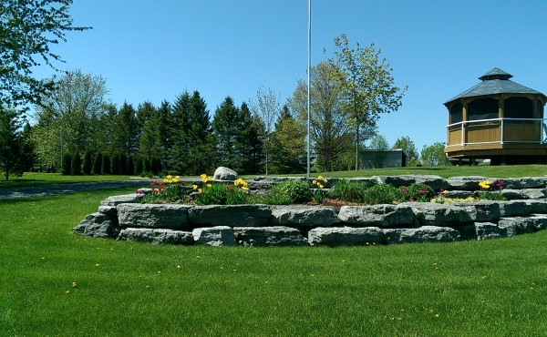 This large block limestone wall makes for a great raised garden bed to welcome visitors to this large property.