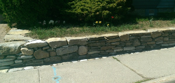 A mixed fieldstone wall gives this small town home a quant look with some curb appeal.