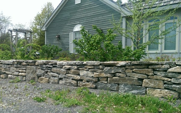 A mixed fieldstone wall provides a nice barrier to this front of this country property.