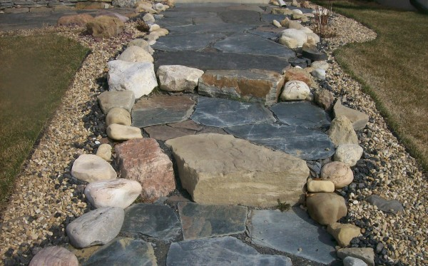 A mixed stone walkway with lots of character welcomes visitors to this home.