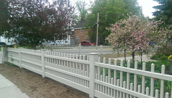 A modern picket style fence provides an attractive barricade for this corner lot. Manufactured block pillars sit on each corner.