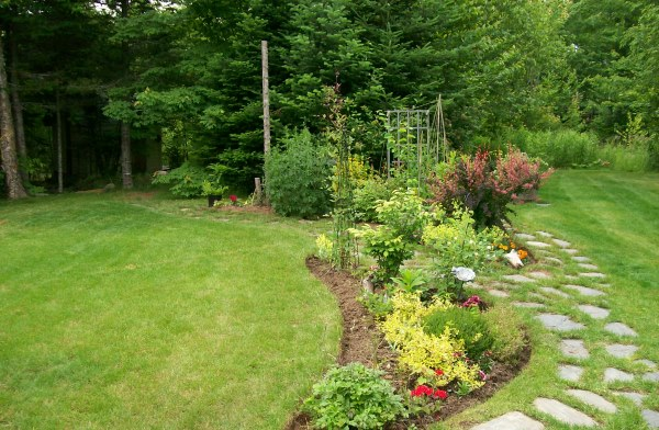 A naturalistic blended theme with garden beds in front of native trees and shrubs left at the time of clearing the lot. This property is less than 3 years old.