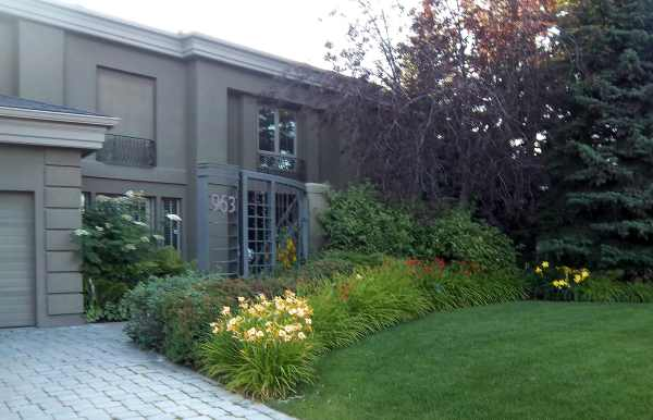 A formal looking home is transformed by this informal front garden. The soft flowing curve with mixed grasses, perennials, and shrubs creates a