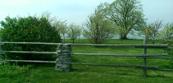 A Wooden fence with natural stone built pillars looks right at home for this large lakeside property.