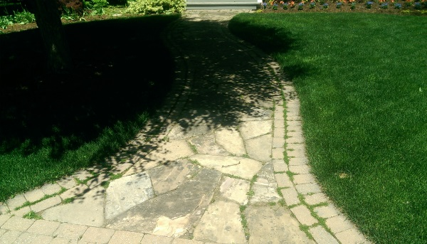 A weathered flagstone front walkway has a creative double brick soldier course to define the edges.