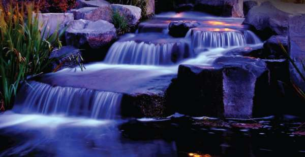A nicely designed multi-cascade water feature is lined with just the right stones and plants.