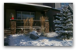 A small frontyard, designed for all seasons. Ornamental grasses and the feature boulders provide year round interest.