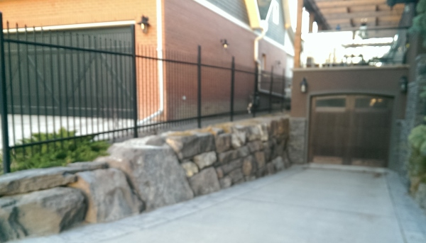 A mixed natural stone retaining wall down the side of a downhill driveway gives lots of character.