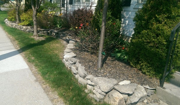 This homeowner used a fieldstone wall to add curb appeal with a low maintenance garden bed. A nice flowing curve along the length of the wall adds a more interesting look.