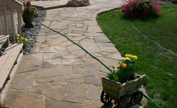 This country yard on an acreage looks much more at home with a dry-laid flagstone walkway leading from the driveway to the front door.