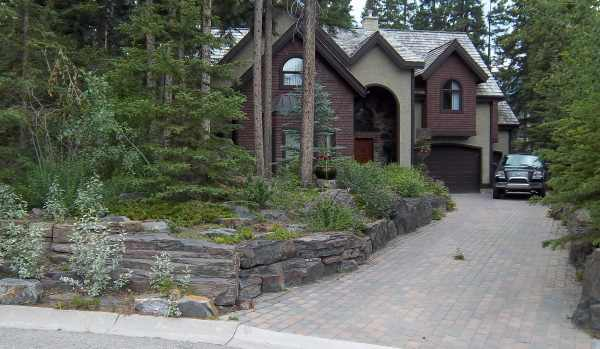 The stone walls and interlocking brick driveway used here are a great way to blend a design into the existing natural landscape.