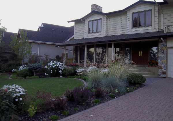 A mixed ornamental grass and perennial garden wrap this front lawn for some great color and front yard curb appeal.