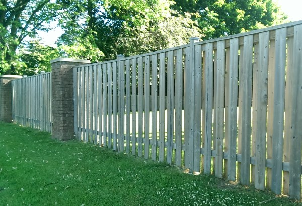 Another option for brick pillars is a wooden fence. They provide a more formal look and solid looking construction.