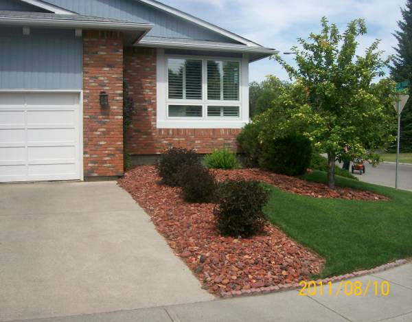 Driveway landscaping on a corner lot with a decorative rock to match the brickwork.