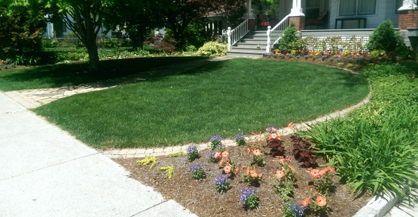 A simple way to define up a front yard circular garden bed with a border of mow over bricks.