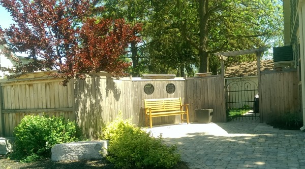 This simple wooden fence has so much character with the top rail trim, windows and the gate arbour.