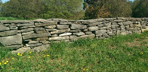 A dry stacked fieldstone wall at the entrance to a large acreage property. Fieldstone provides the weathered look like the wall has been there for centuries.