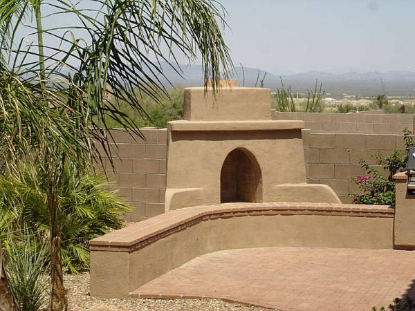 A small patio area for a BBQ and outdoor fireplace well designed to incorporate the distant mountains in the scene while taking the eye off the block privacy wall.