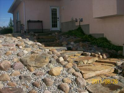 This slope of natural slab steps and a small boulder rock garden is a great way to have a low maintenance slope.