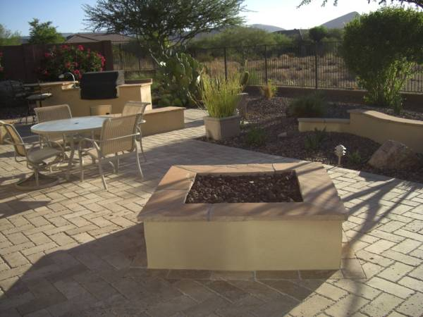 A square firepit is set off to one side of an outdoor kitchen area.