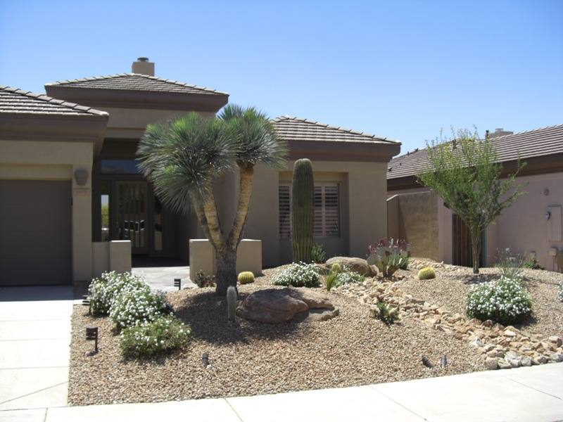 A dry creek bed comes from down the side of the house and splits this front yard, breaking up the sea of gravel.