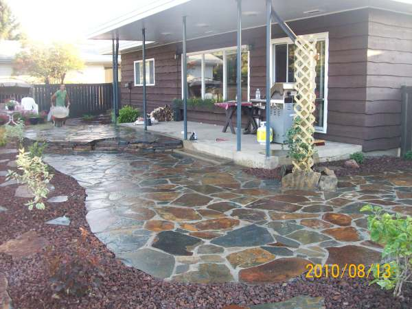 This dry-laid flagstone patio was blended to a lawn using edging and a decorative rock bed.