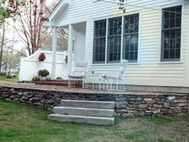 A rustic looking stone wall supports a walkout patio area.