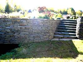 This flagstone wall curves nicely into a set of natural stone steps.