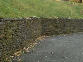 A high retaining wall is used to hold back this steep bank and expand the useable area below it.