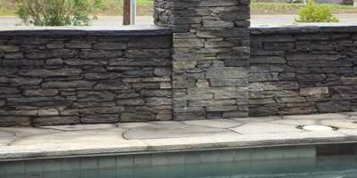 A poolside wall with a pillar are capped with flagstone
