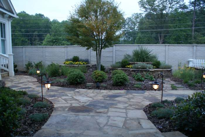Wide natural stone walkway splitting into two smaller walkways that stroll through perennial planted mulch beds.