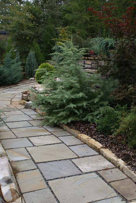 Cut flagstone walkway with a low border of natural stone blocks.