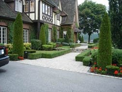 A formal front yard design that is very well manicured.
