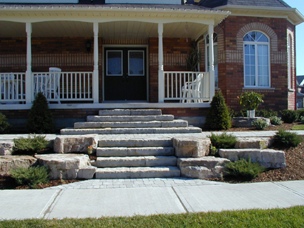 Beautiful stone steps split this low maintenance front yard as they lead to the lead to the front door of this home.