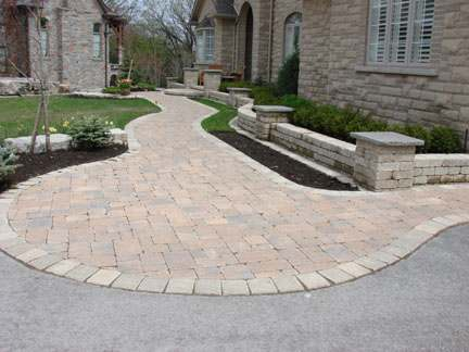 A wide opening tastefully blended into the driveway leads to the front entry of a large house.