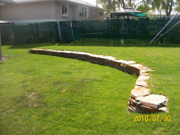 This low retaining wall adds more interest to this yard with a slightly sloped backyard.