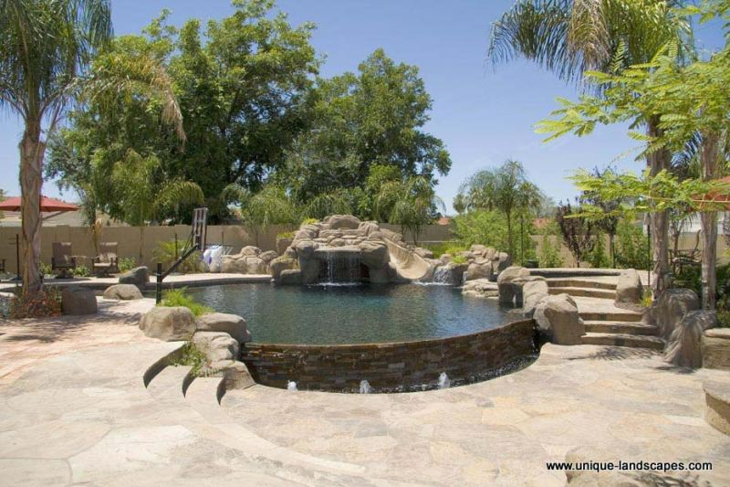 A beautiful flagstone patio with stairs molded into boulder features around this stunning pool.
