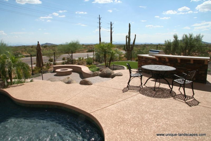Poolside patio with an outdoor kitchen and lower level firepit surrounded by natural desert plants.