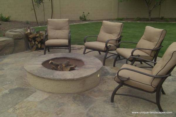 A simple backyard firepit centered in a flagstone patio area.